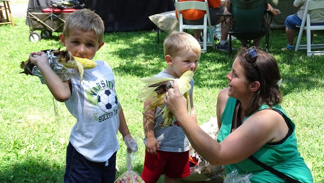 Brothers Landon, left, and Travis Abel take a bite out of GroveFest. Their mother, Abbey Belle, said the festival was fun and educational.