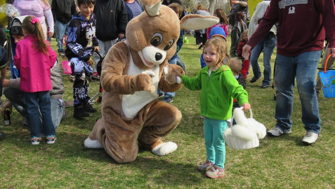 Skylar Pruys, 4, dances the Hokey Pokey with a bunny at the city's annual Easter Egg Hunt.