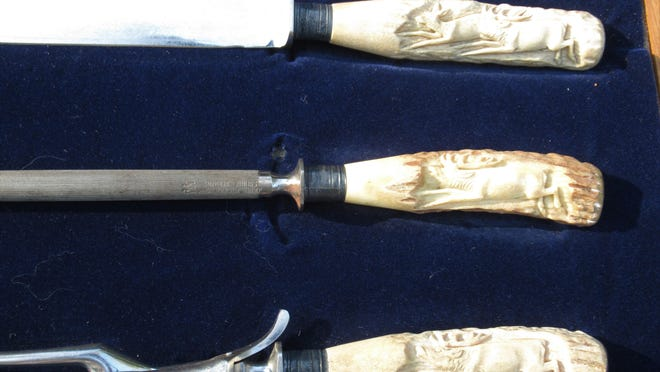 The staghorn antler handles on this carving set are relief carved and not scrimshaw. Scrimshaw is incised or engraved surface decoration done originally by sailors on whales' teeth and other parts of the animal and very highly sought after by collectors.