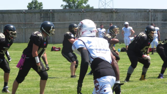 The Burlington Express line up for a play during Sunday's MA8FL semi-pro football game against the Peoria Punishers at the 40&8 Park in Burlington.