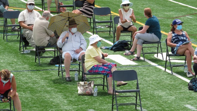 Some residents brought their own shade to Medfield's annual Town Meeting on Saturday, June 27, at the high school football field.