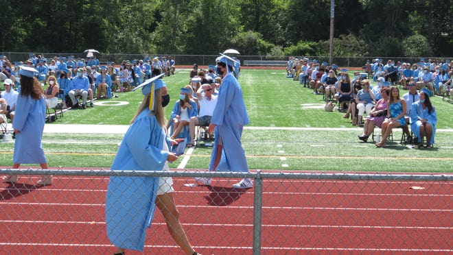 Members of Medfield High's Class of 2020 proceed to and from the podium during their ceremony on July 25.