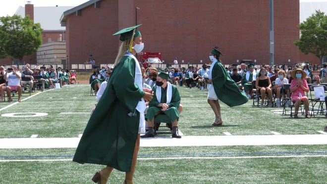 Members of Westwood High's Class of 2020 proceed to and from the podium during graduation ceremonies on Aug. 9.