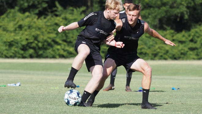 Tormenta FC midfielder Grant Hampton of Savannah controls the ball while being closely marked.