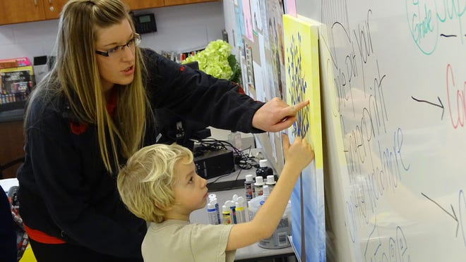 Erika Warren helps Keegan Strong put his thumbprint on a community thumb tree inside Woodmore Elementary School's art room. The Woodmore school district held a grand opening ceremony Sunday for its new K-8 building.
