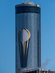 A giant College Football Playoff National Championship Trophy is shown on a downtown hotel in Atlanta, Ga., on Saturday January 6, 2018. (Mickey Welsh / Montgomery Advertiser)
