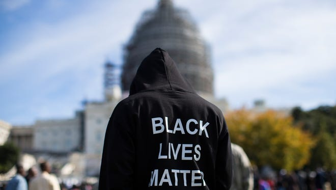 """Neal Blair, of Augusta, Ga., wears a hoodie which reads, """"Black Lives Matter"""" as he stands on the lawn of the Capitol building during a rally to mark the 20th anniversary of the Million Man March, on Capitol Hill, on Saturday, Oct. 10, 2015, in Washington."""