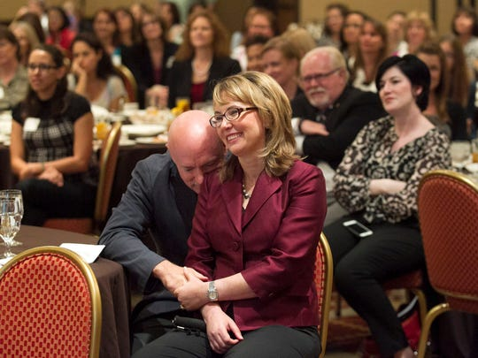 Mark Kelly rests his head against the shoulder of his wife, Gabby Giffords, during the YWCA Tucson Women's Leadership Conference on Sept. 23, 2014.