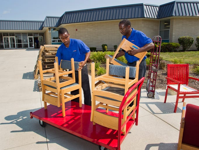Jeremy Gould, left, and David Holman move furniture into Mintonye Elementary School as it near completion of being rebuilt after a tornado last fall Monday, July 21, 2014, at the school near Lafayette.