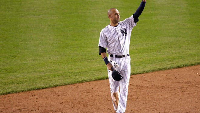 New York Yankees shortstop Derek Jeter waves to fans as he walks around the infield after driving in the winning run against the Baltimore Orioles in the ninth inning.