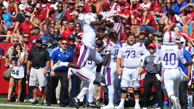 Louisiana Tech safety Xavier Woods makes a leaping interception against Arkansas. The Bulldogs nearly pulled off the upset in a 21-20 loss.