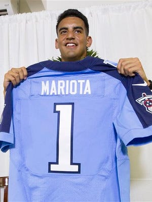 Former Oregon quarterback Marcus Mariota holds up his Tennessee Titians jersey for the media after being selected in the first round with the second pick by the Tennessee Titans on NFL Draft Day Thursday, April 30, 2015, in Honolulu. Mariota along with his family and friends gathered at the Saint Louis Alumni Clubhouse to celebrate his selection in the NFL Draft. (AP Photo/Eugene Tanner)
