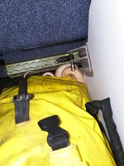 In this Sunday, March 19, 2017 photo, a snake lies beneath a duffel bag on a Ravn Alaska flight between Aniak, Alaska and Anchorage. The snake escaped from a passenger on a previous flight. A flight attendant captured the reptile and placed it in a trash bag and stowed it in an overhead luggage compartment. (Anna McConnaughy via AP)