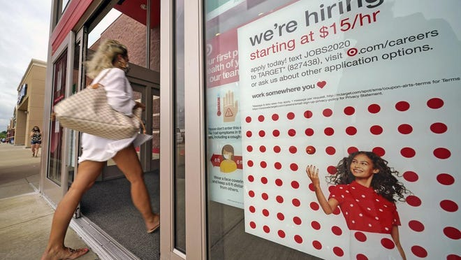 FILE - In this Sept. 2, 2020, file photo, a help wanted sign hangs on the door of a Target store in Uniontown, Pa. Hundreds of thousands of Americans likely applied for unemployment benefits last week, a high level of job insecurity that reflects economic damage from the coronavirus outbreak. Economists expect that 850,000 people sought jobless aid, down from 884,000 the week before, according to a survey by the data firm FactSet.