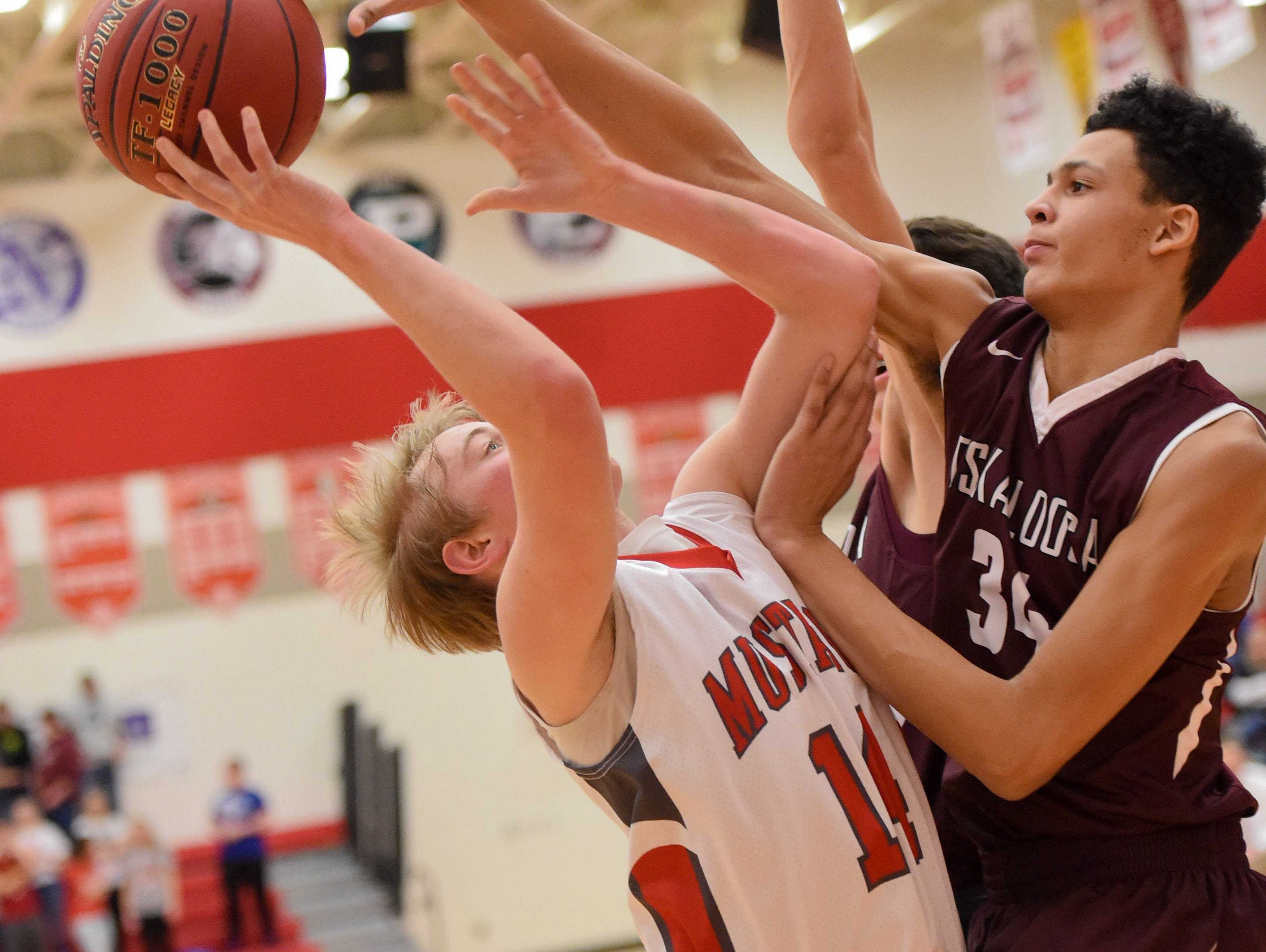 DCG's Jordan Humphreys (14) gets blocked by Oskaloosa's Xavier Foster (34) on Friday, Jan. 27, 2017, during a basketball game between the Dallas Center-Grimes Mustangs and the Oskaloosa Indians at Dallas Center-Grimes High School.