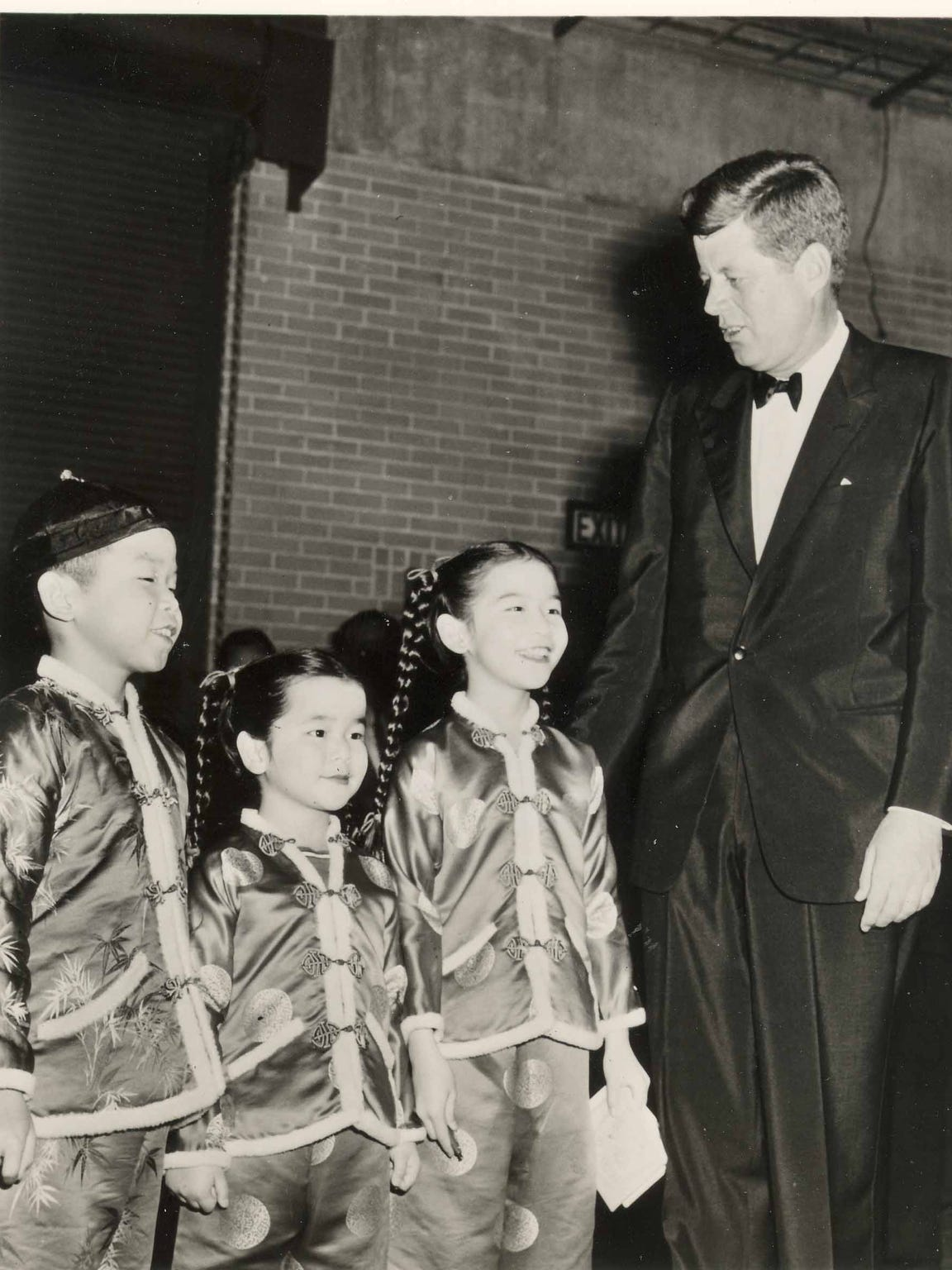 Pres. John F. Kennedy in tuxedo with 3 cast members