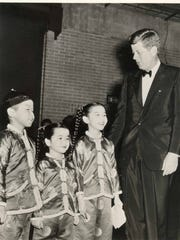 "Pres. John F. Kennedy in tuxedo with 3 cast members (young girls) of ""Girls, Girls, Girls"" starring Elvis Presley at Arie Crown Theater McCormick Place on August 19, 1962."