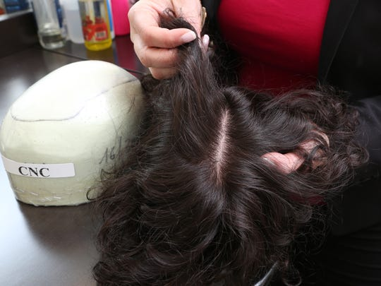 Owner Flora Fuentes shows a hair and scalp prosthetic that was created with 3D technology to replicate a second scalp at  Unique Hair Concepts in Ardsley May 4, 2017.