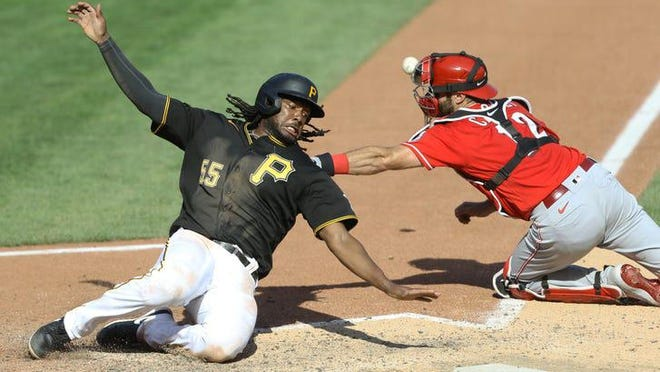 Pittsburgh Pirates designated hitter Josh Bell (55) slides across home plate to score the tying run in the ninth inning as Cincinnati Reds catcher Curt Casali (right) cannot get the throw during a Major League Baseball game at PNC Park, Pittsburgh, on Sunday Sept. 6, 2020. The Pirates won 3-2.