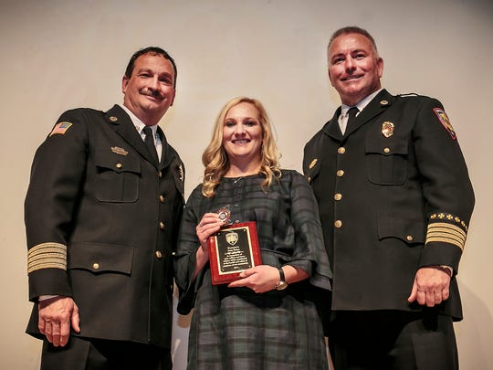 Amy Nolen with Fire Rescue Chief Mark Foulks, left, and Deputy Chief Roger Toombs