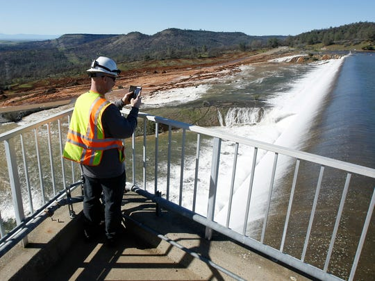 Jason Newton, of the Department of Water Resources, takes a picture of water going over the emergency spillway at Oroville Dam Saturday, Feb. 11, 2017, in Oroville, Calif. Water started flowing over the emergency spillway at the nation's tallest dam for the first time Saturday after erosion damaged the Northern California dam's main spillway.