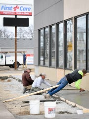 Concrete workers (L-R) Chris Gobin, Greg Collins and Cody Hunt finish out a sidewalk in front of the new First Care Urgent Care Clinic at 230 North Green Street in Henderson Wednesday, February 1, 2017.