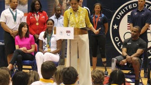 First lady Michelle Obama addresses a crowd at American University's Bender Arena on March 13, while Samantha Cameron (pink top) looks on.