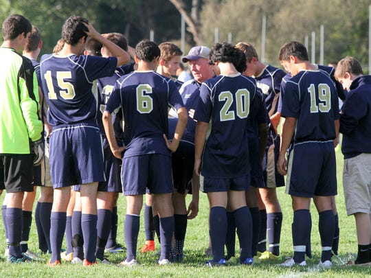 The Elmira Notre Dame boys soccer team gathers together around head coach Brian Adams at halftime of a win at Watkins Glen on Sept. 16.