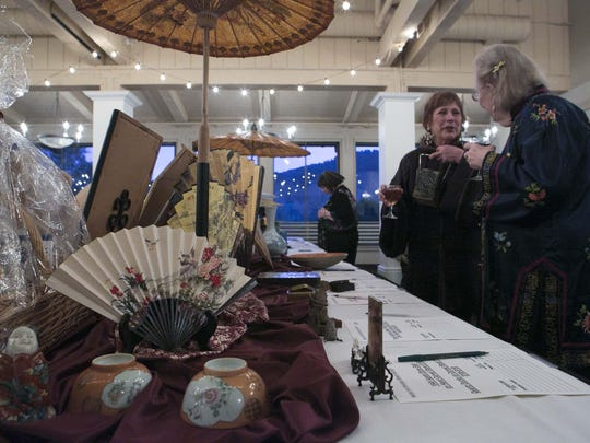 Attendees gather around the silent auction table to converse during the Asian Art Society of Monterey Bay annual gala at Rancho Canada Golf Club on Tuesday, January 31, 2017 in Carmel-By-The-Sea, Calif.