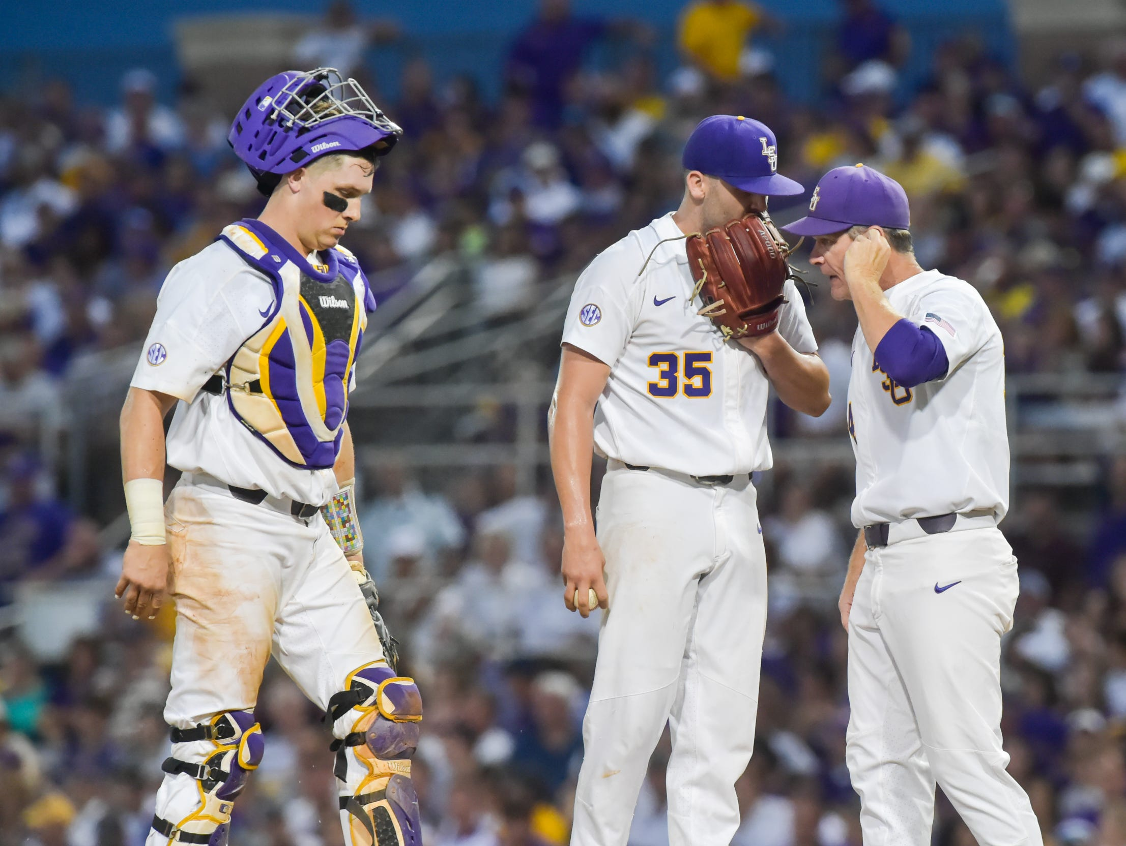 Pitching coach Alan Dunn meets with Alex Lange during the first inning as Mississippi State takes on LSU in the NCAA Super Regional at Alex Box Stadium in Baton Rouge Saturday, June 10, 2017.