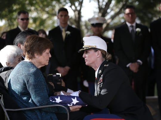"""Lucia Hernandez receives the casket flag from her husband Enrique """"Hank"""" Hernandez's casket during a graveside service for the Marine Vietnam veteran Monday at Fort Bliss National Cemetery."""