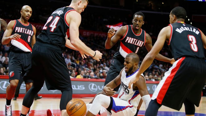 Los Angeles Clippers' Chris Paul falls while losing grasp of an offensive rebound as he is surrounded by Portland Trail Blazers', from left to right, Gerald Henderson, Mason Plumlee, Al-Farouq Aminu, and C.J. McCollum during the first half of an NBA basketball game, Monday, Nov. 30, 2015, in Los Angeles.