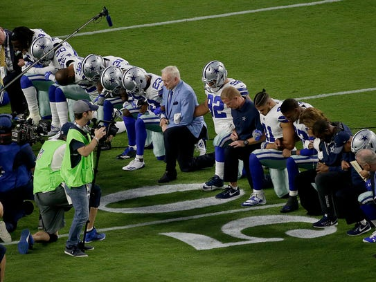 The Dallas Cowboys, led by owner Jerry Jones, center,