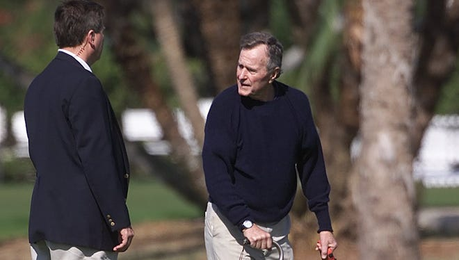 Former president, George Bush Sr. talks to an unidentified secret service agent while taking his dog for a walk on the golf course at The Gasparilla Inn on Dec. 28, 2000. ANDREW WEST/The News-Press