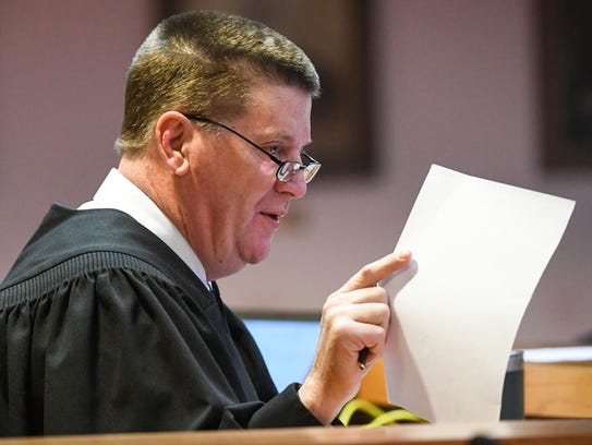 Judge Cordell Maddox  holds a doctor's note about Debra Sheridan in the Anderson County Courthouse on Friday. Sheridan was sentenced to two years in prison for violating probation by having a gun.