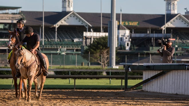 Justify is lead off the track by Jimmy Barnes, assistant trainer for Bob Baffert Stables, following a workout at Churchill Downs. June 4, 2018