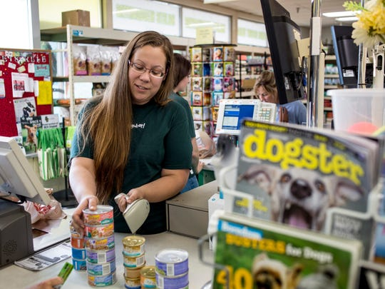 Store Manager Brandy Braley checks out and bags items for a customer Tuesday, August 16, 2016 at Pet Supplies Plus in Fort Gratiot. The store will be closing in September.