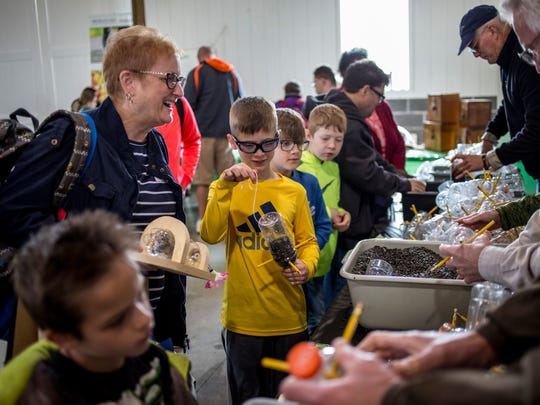 Collin Grove, 9, of Clay Township, makes a bird feeder out of a plastic bottle and pencils with his grandmother, Teri Klunzinger, of Clarkston, at the Blue Water Audubon Society booth during the Earth Fair Friday, April 28, 2017 at Goodells County Park.