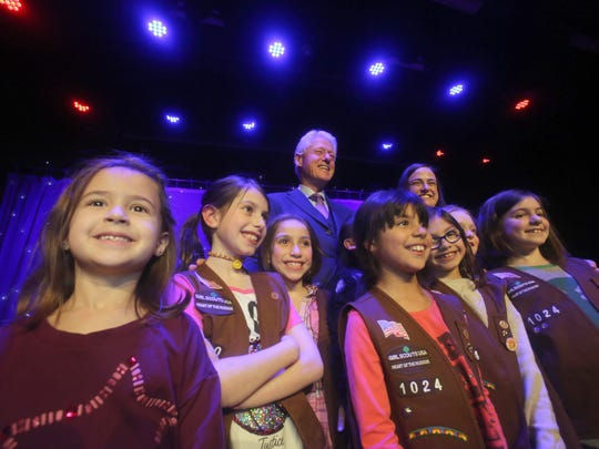 Former President Bill Clinton takes a photo with local