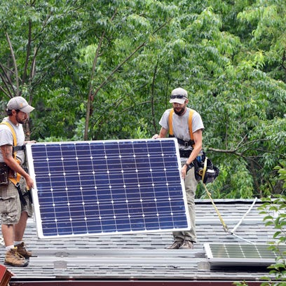 Electricians Graham Horne, left, and Brandon Taylor, of Sugar Hollow Solar, install solar panels to produce about 4 kilowatts of electricity on the roof of a home off Courtland Avenue in downtown Asheville.