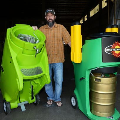 Jim Hager, of Feelfree Kayaks, stands with his new line of Chilart beer keg coolers at the Feelfree Kayaks headquarters in Swannanoa Tuesday afternoon. The cooler pictured, left, shows his new design of metal coils made to keep beer cooler.