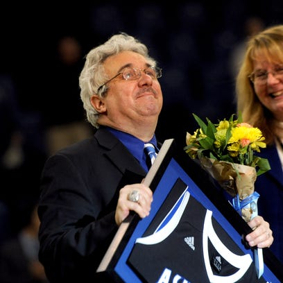 Mike Gore and his wife Lisa soak in a standing ovation he received at Kimmel Arena in February after the announcement that he was retiring as UNC Asheville's assistant athletic director and head of sports information.