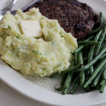 This Feb. 2, 2015 photo shows mashed potatoes flecked with scallions and topped with butter in Concord, N.H.