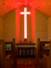 A red glass cross lights the altar to the Little Prayer Church in Newburgh.