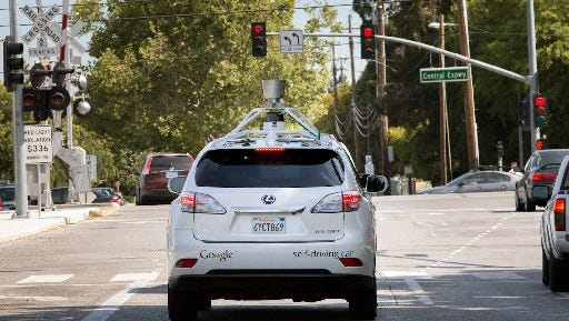 This Lexus RX outfitted with Google's self-driving technology navigates along a street in Mountain View, Calif.