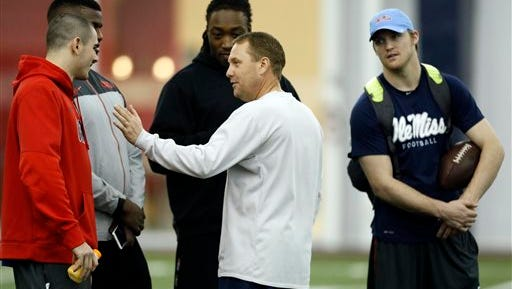Mississippi football coach Hugh Freeze, second from right, speaks with players quarterback Chad Kelly, left, defensive ends Channing Ward, second from left, Fadol Brown, center, as former Mississippi quarterback Bo Wallace listens in during Pro Day at Mississippi in Oxford, Miss., Thursday, March 5, 2015. The event showcases players for the upcoming NFL football draft. (AP Photo/Rogelio V. Solis)