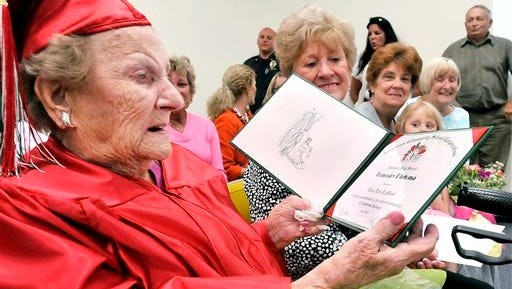 Wearing her cap & gown Lora Lois LeMond White Hardy, 99, looks over the honorary diploma from Anderson High School in Anderson, Ind. she received Tuesday May 12, 2015 from the Anderson Community Schools board of trustees.  Lora, who turns 100 on May 28, had to quit school her senior year in 1933 just four credits shy of her diploma to go to work to help support her family.