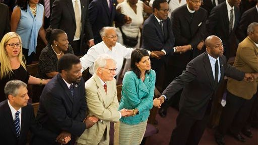 South Carolina Gov. Nikki Haley, center right, joins hands with Charleston Mayor Joseph Riley, left, and Sen. Tim Scott, R-S.C., right, at a memorial service at Morris Brown AME Church for thepeople killed Wednesday during a prayer meeting inside the historic black church in Charleston, S.C., Thursday, June 18, 2015. Police arrested 21-year-old suspect Dylann Storm Roof Thursday in Shelby, N.C. without resistance. (AP Photo/David Goldman)