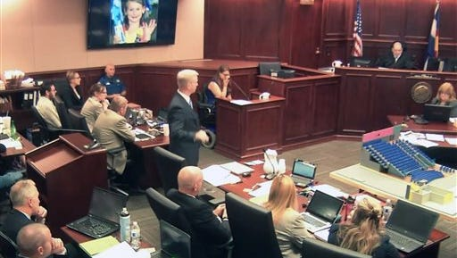 In this image taken from video, Ashley Moser, center top, who lost her 6-year-old daughter Veronica in the 2012 Colorado movie theater mass shooting, cries while testifying as a picture of her slain daughter is shown, top, during the trial of theater shooter James Holmes, pictured at top left, in Centennial, Colo., Friday, June 19, 2015. With the testimony of Moser, who was paralyzed and suffered a miscarriage in the attack, the prosecution rested its case. (Colorado Judicial Department via AP, Pool)