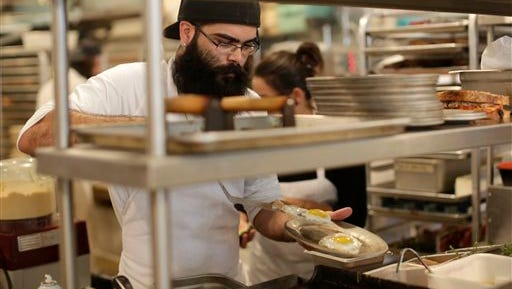 In this June 5 file photo, sous chef Johnny Bacon places fried eggs on a plate while filling an order at Zak the Baker, in Miami. The Labor Department released second-quarter productivity data Wednesday.
